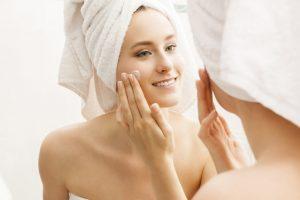 鏡を見ながらクリームを塗る外国人女性